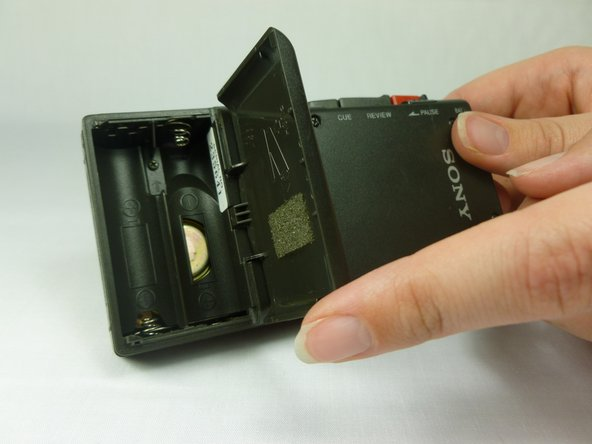 Remove the battery cover by first tilting it so it is at a right angle with the rest of the device.