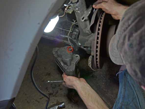 Use an open-end wrench to loosen the 11 mm fitting where the brake hose attaches to the caliper.