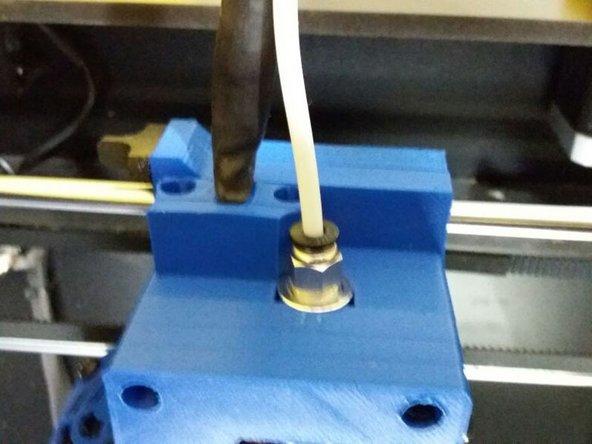 Com as mãos, puxe o tubo PTFE do cabeçote, pressionando a parte preta da peça onde o tubo está encaixado.