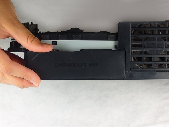 Image 1/1: Pry and remove the expansion bay cover away from its posts on the bottom case.