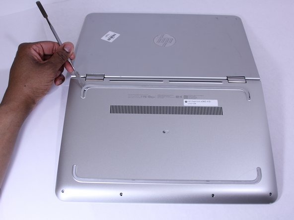 Use a Metal Spudger and  remove the rubber foot closet from the bottom  of the  laptop.