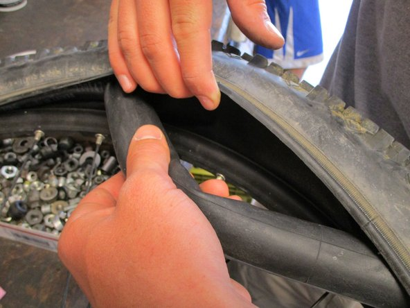Image 3/3: Remove the rest of the tire and the tube from the rim.