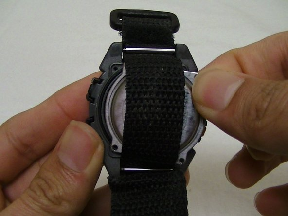Gently pull away the metal covering away from the watch.
