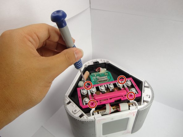 Unscrew the four screws with a Phillips #0 Screwdriver from the pink button sheet.
