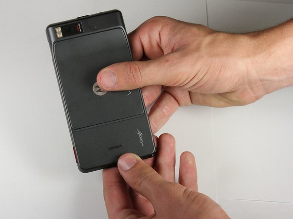 Place thumb on the back cover, and push down towards the bottom of the device.  Once the cover releases, pull it away from the phone and set it aside.