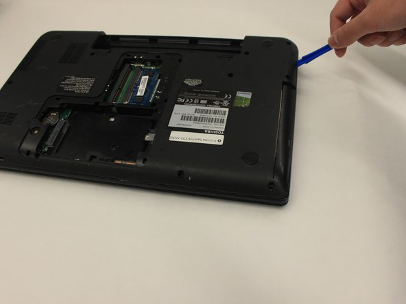 Use a nylon spudger or plastic opening tool to carefully wedge the casing apart and remove the back plate of the laptop.