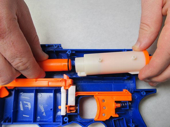 Remove white air chamber by depressing the orange trigger apparatus and pulling backwards off of the barrel.