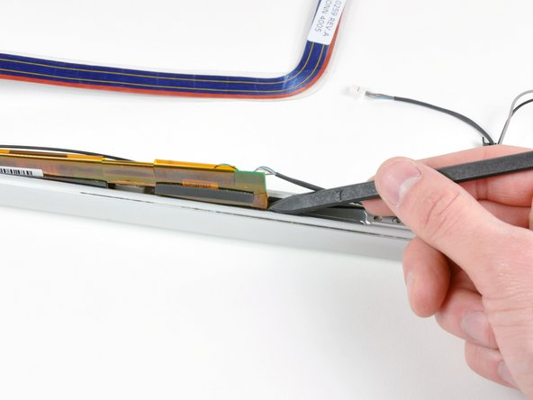 Use the tip of a spudger to lift the display inverter enough to grab it with your fingers.