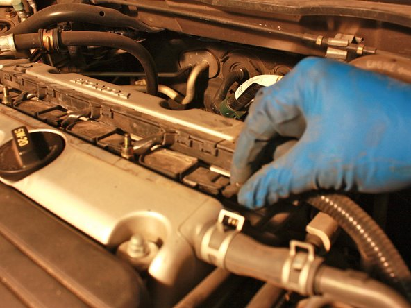 Remove the spark plug wire by pinching the locking tabs on either side of it and pulling it out.