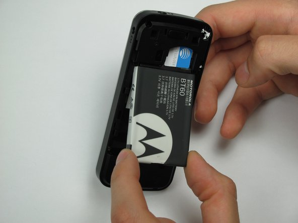 Pinch the sides of the bottom of the battery and pull upward.