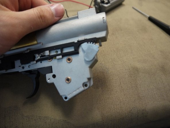 Image 1/3: Place the right side selector plate back in place, aligning the teeth properly. Note that you will have to hold these parts in place while placing the gearbox back in the receiver.