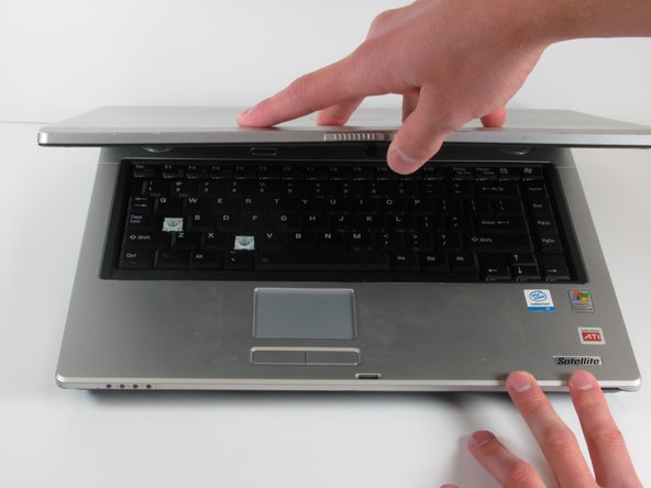 Image 3/3: Open the laptop by lifting the screen up while holding the tab in place.