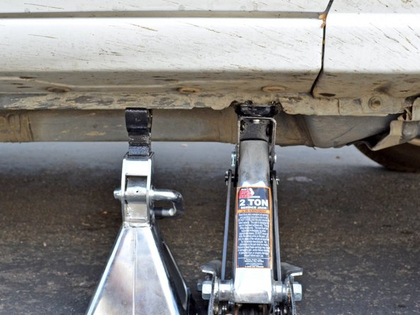 Image 1/2: Slowly lower the jack so that the car is resting on the jack stand. Remove the jack.