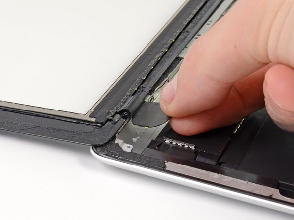 Image 1/1: Using your fingers, pull the digitizer ribbon cable out of its recess in the aluminum frame.