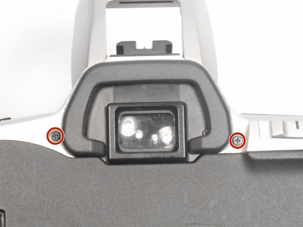 Remove the (2) black Phillips #00 5mm screws that lie on either side of the view finder.