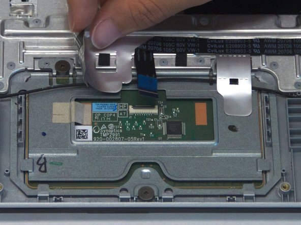 Peel up the silver tape adhering the touchpad cable to the case, revealing two screws underneath.