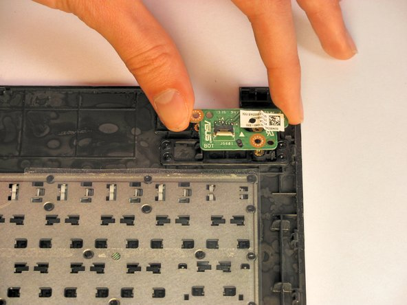 Remove the power button assembly by firmly grasping it from both sides and lifting it off of the keyboard plate cover.