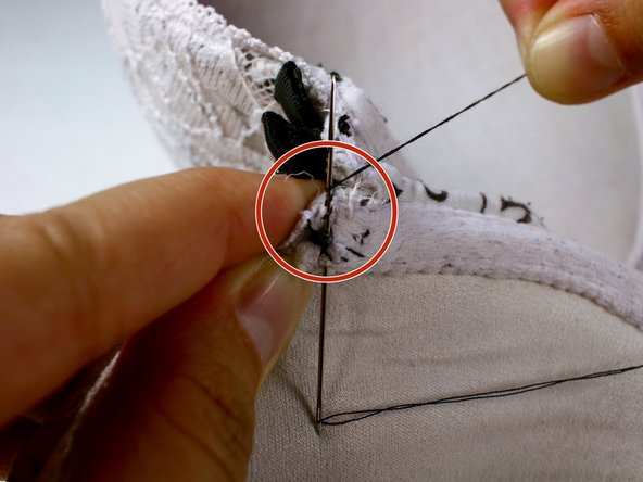 Near your first incision,  where the knot is, insert the needle into the fabric halfway through.