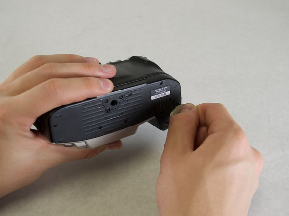 Use the edge of a coin to twist open the battery compartment on the bottom of the camera. (Twist counterclockwise)