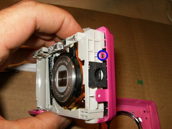 Image 3/3: Remove this screw on the right side of the camera. Keep it separate from the 4 screws previously removed. The are of different length