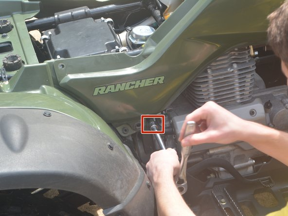 Use a wrench with a 10 mm socket to remove the hex bolt that secures the green plastic panel on the right side of the four wheeler.
