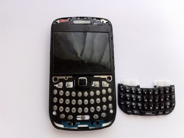 Image 3/3: Using tweezers, remove the keyboard buttons from the phone.