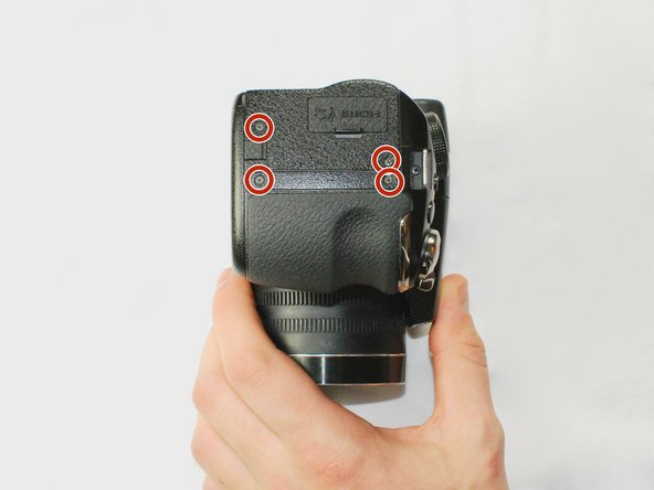 Remove the four 3.5 mm Phillips #1 screws in these positions on the right side of the camera with a screwdriver.