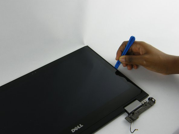 Use your plastic opening tool to pry the LCD back cover from the display panel.