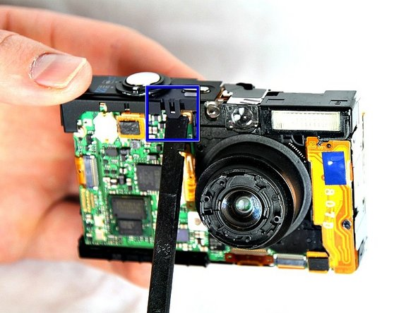 Using the spudger, take off the shutter button by prying the small tab on the front side of the camera.