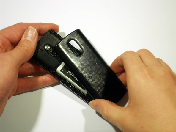 Using your thumb, press down on the back of the device in a downward motion to open the back cover.