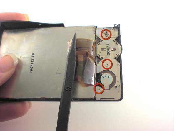 On back of LCD screen, locate the three screws underneath the ribbon and remove them.