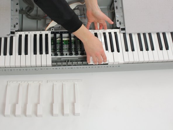 Image 2/2: Push keys away from screws and pull up