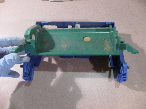Repeat on the other arm. The green brush cage assembly will lift out of the blue housing.