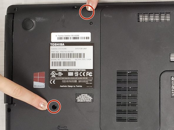 Remove the two 5-mm screws near the disk drive on the back panel. These two screws are above and below the manufacturer's sticker.