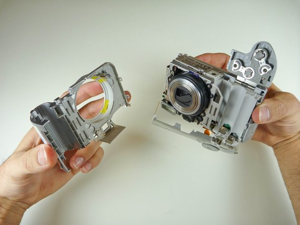 With the camera upside down, pull the  front case's side that is closest to you, in an  outward movement.