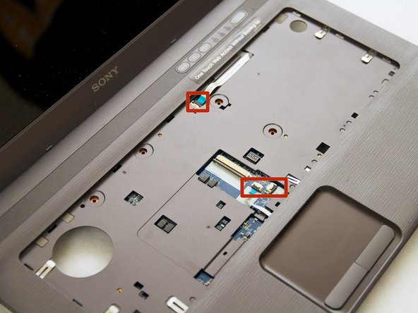 Remove the highlighted ribbon cables from their place underneath the keyboard. To do so, lift up on the black clamps to release the cables.