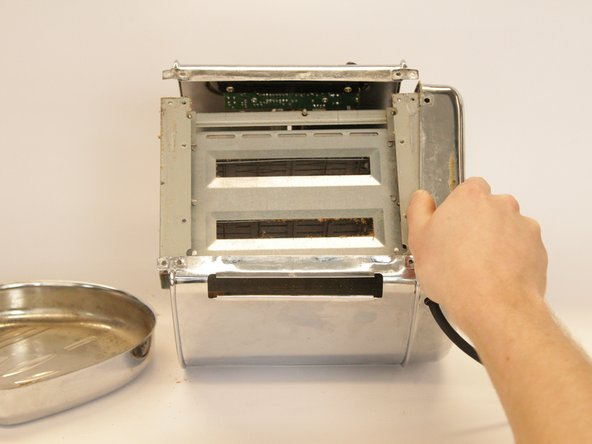 The other side plate cannot be removed entirely, as the cable is still attached.