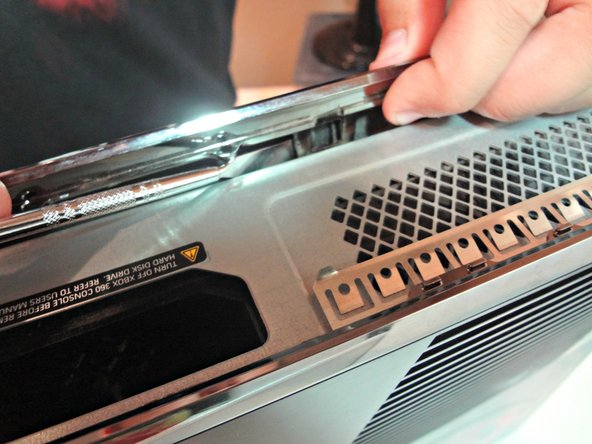 Rotate the tool away from the Xbox prying open the bottom plate. Continue that step for all the remaining clips.