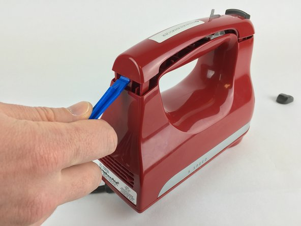 Use a plastic opening tool to remove the long plastic piece