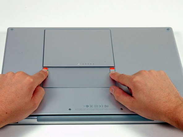 Image 1/1: Use your fingers to push both battery release tabs away from the battery, and lift the battery out of the computer.