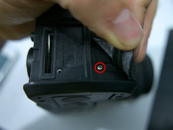 Photo 1: a last 5 mm screw sits under the rubber grip near the base of the camera