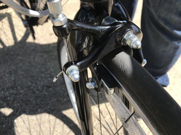 Tighten the barrel adjuster at the brake caliper.