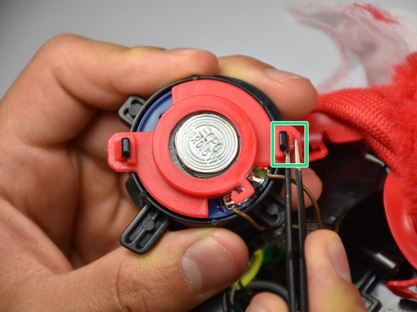 Use the blunt tweezers to pinch the latch on the speaker's casing. Detach the speaker from the both latches on both sides and remove the speaker's casing.