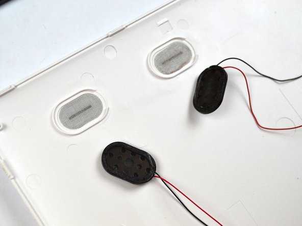 Remove the old speakers from the back cover with the plastic prying tool.