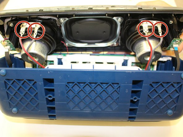 Once you have gotten to the internal parts of the speaker, there are seven wires connecting the speaker plate to the body of the speaker. Pinch the release tabs at the top of each of the four main wires to remove them.
