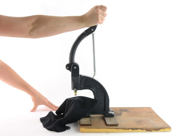 With the fabric aligned, pull the handle of the hand press down in one continuous motion.