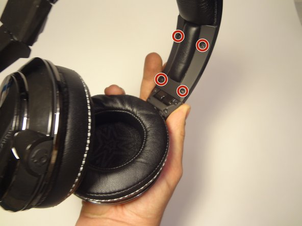 Rotate the headphones so that one of the speaker cups are facing you. Remove the four Phillips 3 mm screws along the headband cover.