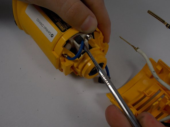Image 1/2: While holding the spring out of the way, use a pointed spudger to slide the carbon brush up out of the guide.