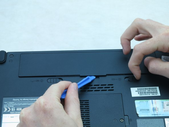 While holding onto the latch, use a plastic opening tool to lift and remove the battery bay cover.