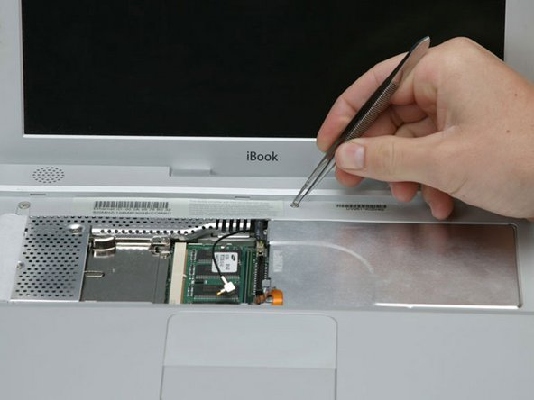 Image 1/1: Use tweezers (or a refrigerator magnet) to remove the magnet covering a Phillips screw near the middle of the computer.